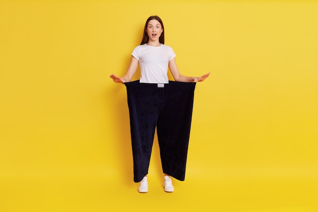 Girl showing weight loss, astonished girl with opened mouth, lady in white t shirt wearing old black pants in huge size, standing isolated over yellow wall.