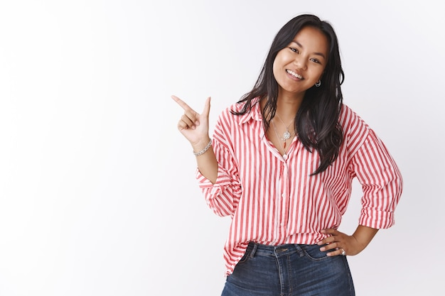 Girl shows best choice for you. portrait of happy charming young 20s asian female holding hand on waist as pointing at upper left corner smiling and tilting head, suggesting awesome promo