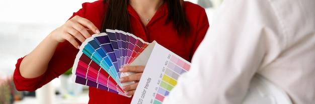 女の子は、ビルダーパレットのトレンディな色2020を示しています。石膏の塗装と広いパレットの色合いを使用します。女性デザイナーは、アパートの改装のための選択色を提供しています。インテリアのパレットカラーを選択