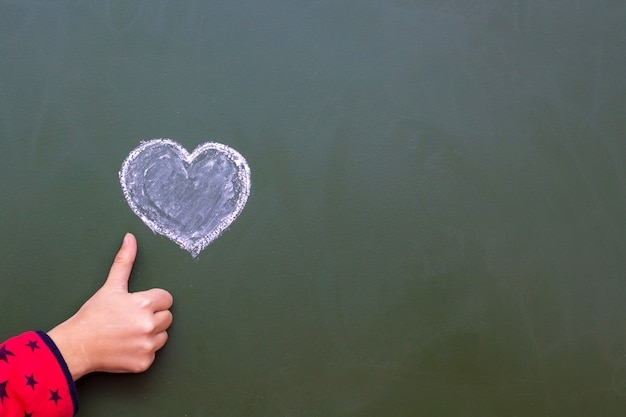 The girl shows by hand ok next to the heart drawn with the chalk