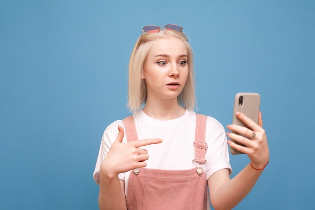Girl shows finger on the smartphone in her hand and looks at the screen
