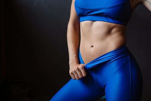 여자는 그녀의 펌핑 배꼽 프레스를 보여줍니다. 식이 요법과 무거운 운동, 슬림 허리 후 운동 몸