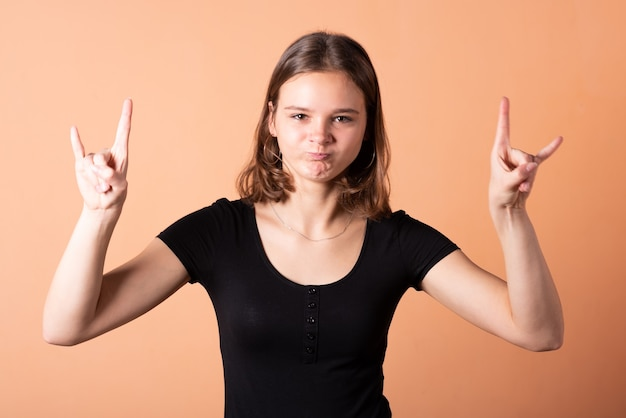 A girl shows a rocker goat, on a light orange background. for any purpose.