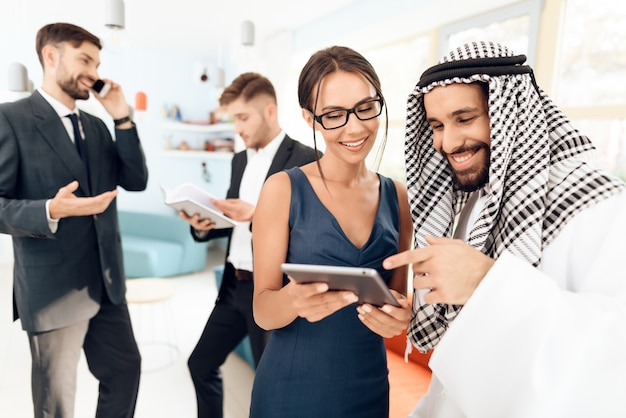 Girl shows something to a man in arabic clothes on a tablet.