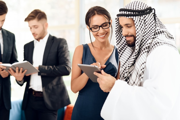 A girl shows something to a man in arabic clothes on tablet.