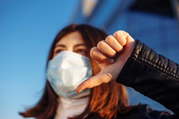 Girl shows thumb down and dislikes coronavirus worldwide pandemia