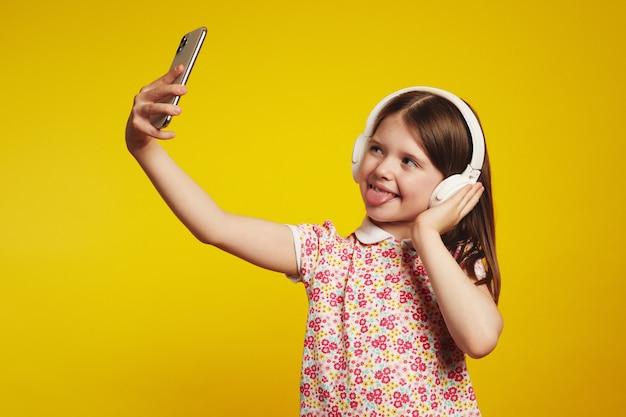 Девушка показывает язык и делает селфи на смартфоне, слушает музыку в
