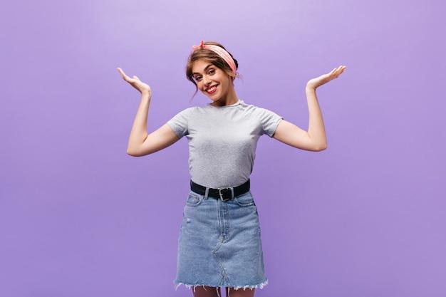 Ragazza che scrolla le spalle e posa. sfondo viola. giovane donna fresca sorridente in maglietta grigia che esamina la macchina fotografica sul contesto isolato.