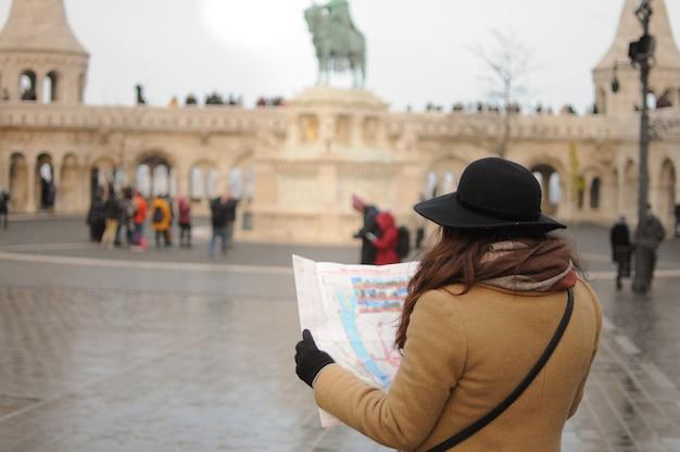 소녀 관광. 여성 혼자 지도를 보고 도시를 봅니다. 겨울 추운 시간입니다. 해외 여행.