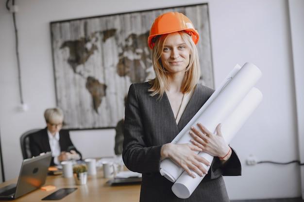 소녀는 문서에 서명합니다. 빨간 헬멧에있는 여자. 사무실에서 일하는 managerl.