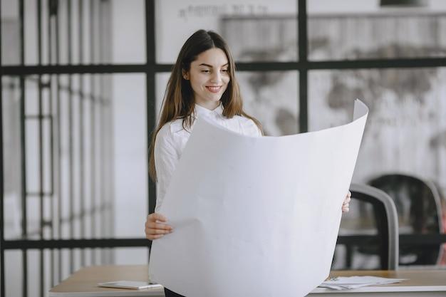 소녀는 문서에 서명합니다. 테이블에 앉아 레이디입니다. 사무실에서 일하는 관리자.