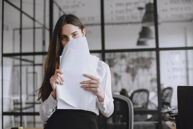 소녀는 문서에 서명합니다. 사무실에서 일하는 관리자. 카메라를보고 레이디입니다.