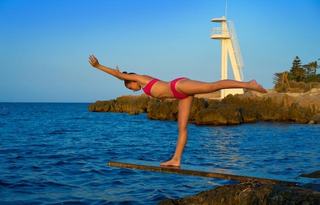 Girl silhouette at beach sunset gymnastics