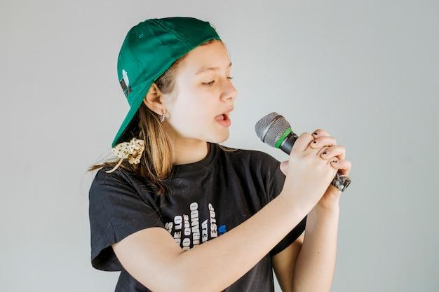 Девушка петь песню с микрофоном на сером фоне