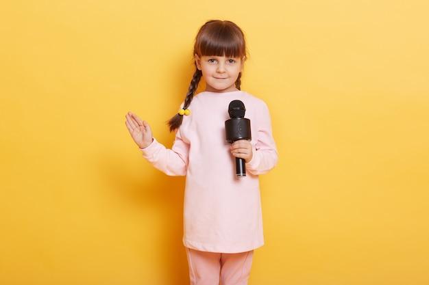 マイクを持って歌い、手のひらをカメラに向けて振る女の子、笑顔、かわいくて魅力的な表情、カメラを見る、カジュアルな服を着て、誰かのためにコンサートをアレンジするおさげの子供。