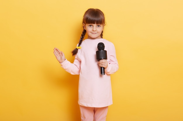 Girl singing with microphone and waving palm to camera, smiles, looking cute and charming, looks at camera, wearing casual clothing, kid with pigtails arranging concert for somebody.