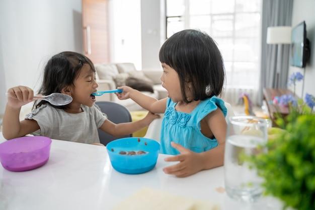 朝食をとりながら、お互いに餌をやる女の妹
