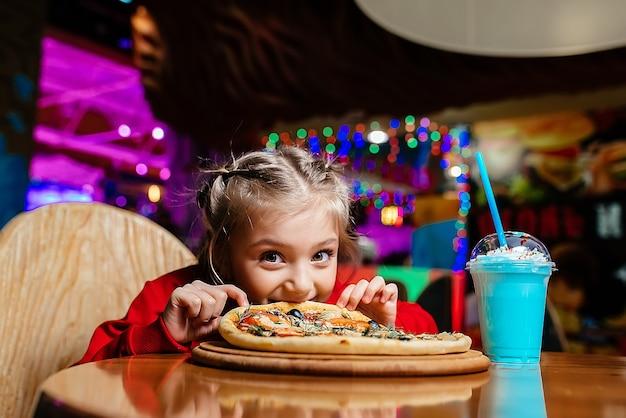 Девушка сидит за столом и ест пиццу