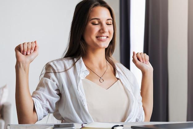 女の子はホームオフィスの机に座って、彼女の手で楽しいジェスチャーを示しています。