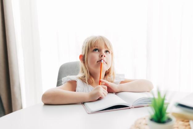 소녀는 테이블에 앉아서 흰색 노트북에 씁니다.