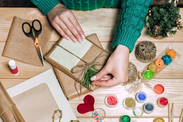 Девушка сидит за столом и заворачивает рождественские подарки