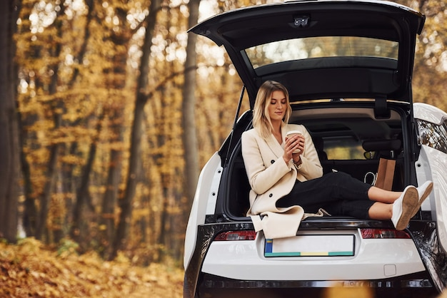 Girl sits on the back of car. modern brand new automobile in the forest.
