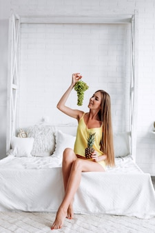 The girl sits on the bed and holds grapes and pineapple in her hand