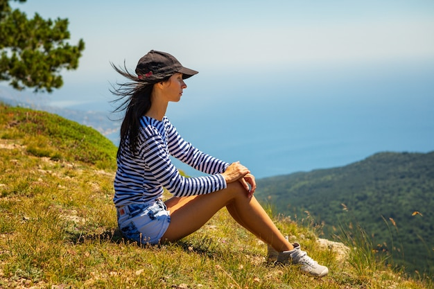 The girl sits in the cap on a cliff with beautiful views of the mountains and sky, travel concept