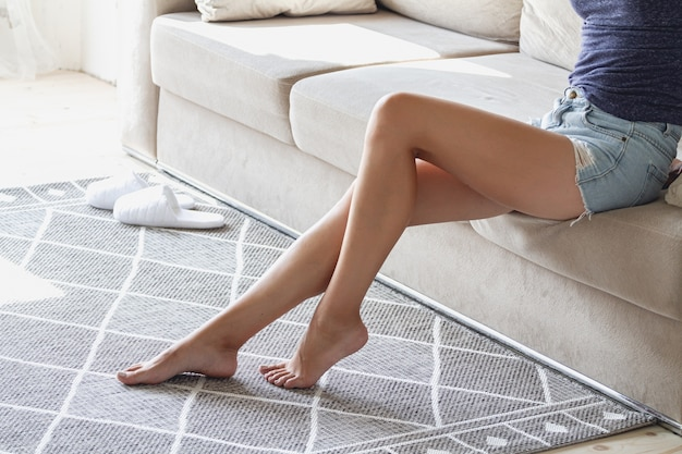 The girl sits on the couch and her legs are without slippers on