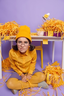 Girl sits crossed legs looks irritated dressed in stylish outfit work in home office makes creative task has real mess piles of cut paper on purple