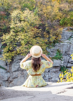 The girl sits on the edge of the canyon