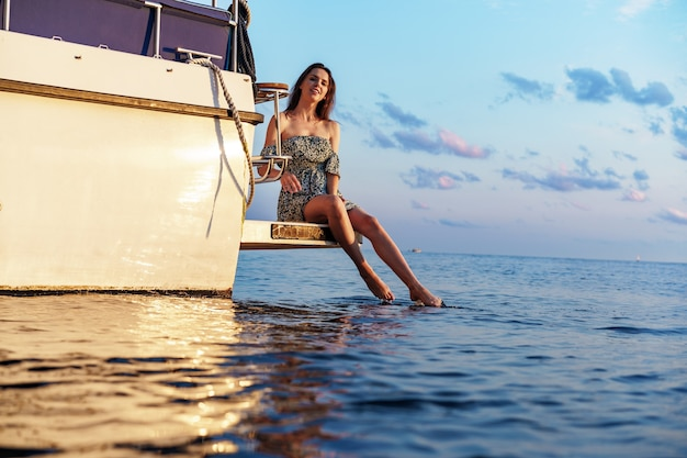 Girl sits on the edge of the yacht with legs splashing in sea water, close up