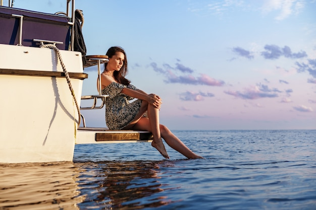 Girl sits on the edge of the yacht with legs splashing in sea water