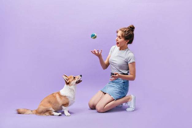 Girl sits on floor and plays with dog. happy young woman in white sneakers posing with ball and corgi on purple background.