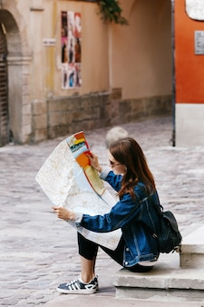 Girl sits on the footsteps looks at the touristic map
