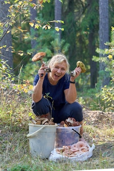 The girl sits in front of buckets of mushrooms the blonde holds large boletus in her hands