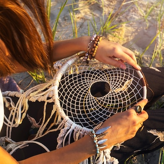 A girl sits on the grass and holds a dream catcher