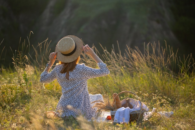 The girl sits in the grass in nature. the girl looks at the sunset. the girl is resting in nature with a basket of food. picnic in nature.