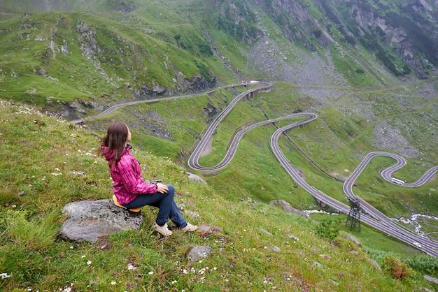 Девушка сидит на камне, наслаждаясь прекрасным горным пейзажем. шоссе трансфагарашан, самая красивая дорога в европе, хребет фэгэраш