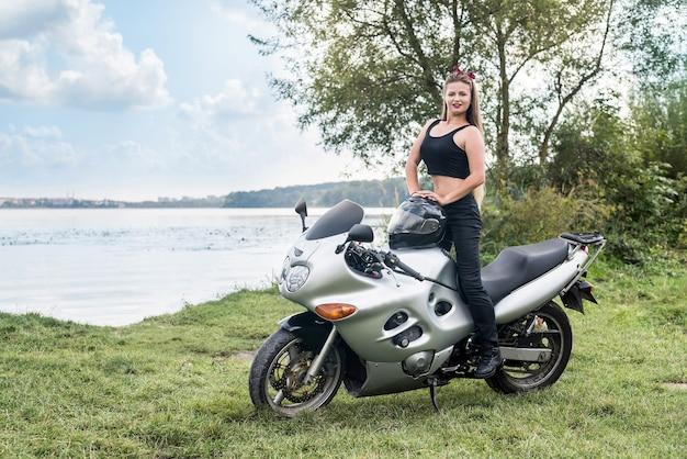 소녀는 호수 배경에 스포츠 자전거에 앉아