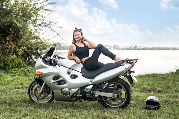 女の子は湖の背景にスポーツバイクに座っています