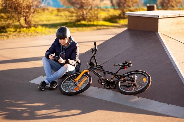 소녀는 일몰에 헬멧에 아스팔트에 자전거 스탠드에 앉아