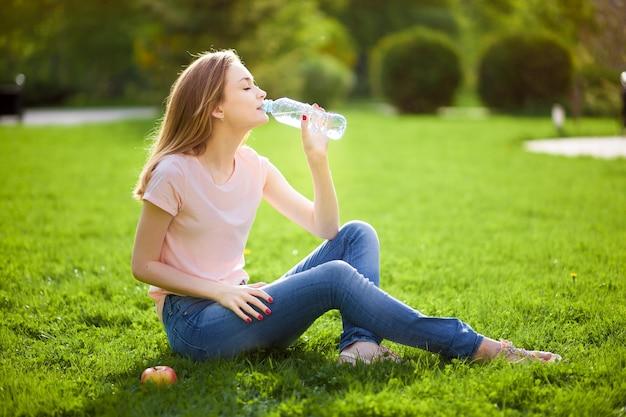 Девушка сидит на лужайке и пьет воду