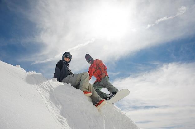 Девушка сидит на снегу на склоне холма, а парень готовится спуститься на сноуборд