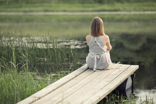 Girl sits on the pier by the lake and dreams of life