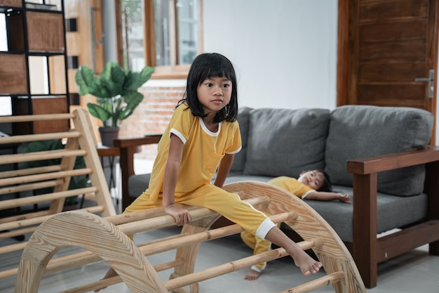 A girl sits on a pikler climbing toy with a baby in the background playing on the sofa at home