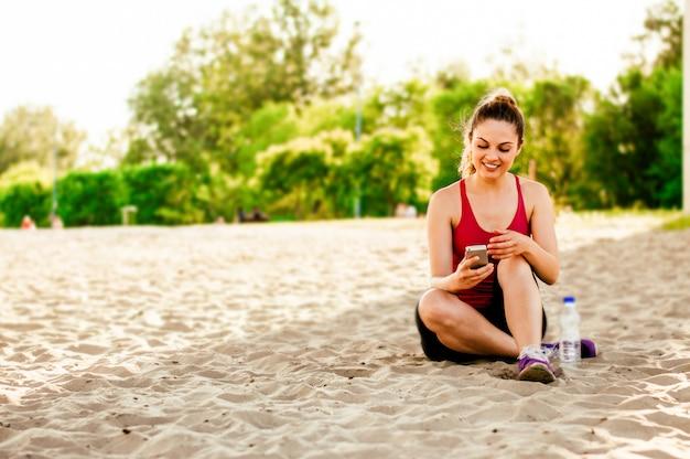 Girl sits on sand and enjoys the phone