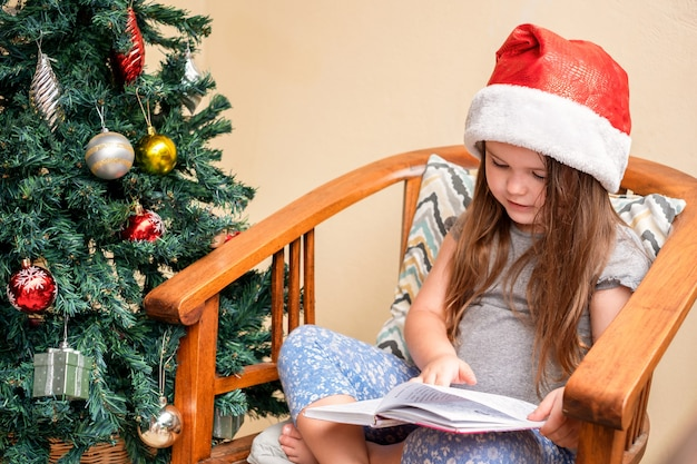 The girl sits in a santa cap near the christmas tree