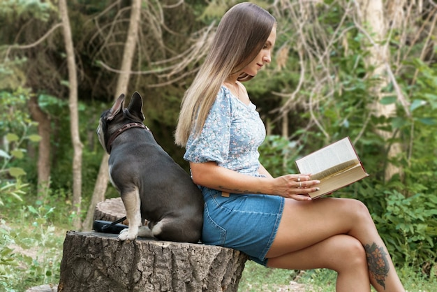A girl sits sideways to the viewer on a tree stump and reads a book a french bulldog sits behind