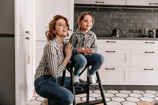 Girl sits on stairs and her mother poses next to against background of kitchen.